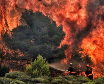 TOPSHOT - Firefighters try to extinguish flames during a wildfire at the village of Kineta, near Athens, on July 24, 2018. - Raging wildfires killed 74 people including small children in Greece, devouring homes and forests as terrified residents fled to the sea to escape the flames, authorities said Tuesday. (Photo by Valerie GACHE / AFP) / The erroneous mention[s] appearing in the metadata of this photo by ANGELOS TZORTZINIS has been modified in AFP systems in the following manner: [--VALERIE GACHE-] instead of [--ANGELOS TZORTZINIS-]. Please immediately remove the erroneous mention[s] from all your online services and delete it (them) from your servers. If you have been authorized by AFP to distribute it (them) to third parties, please ensure that the same actions are carried out by them. Failure to promptly comply with these instructions will entail liability on your part for any continued or post notification usage. Therefore we thank you very much for all your attention and prompt action. We are sorry for the inconvenience this notification may cause and remain at your disposal for any further information you may require. (Photo credit should read VALERIE GACHE/AFP/Getty Images)
