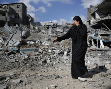 A Palestinian woman weeps as she walks amid destroyed buildings in Beit Hanoun town, which witnesses said was heavily hit by Israeli shelling and air strikes during an Israeli offensive, in the northern Gaza Strip July 26, 2014. A 12-hour humanitarian truce went into effect on Saturday after Israel and Palestinian militant groups in the Gaza Strip agreed to a U.N. request for a pause in fighting and efforts proceeded to secure a long-term ceasefire moved ahead. REUTERS/Finbarr O'Reilly (GAZA - Tags: POLITICS MILITARY CIVIL UNREST) - RTR4071S
