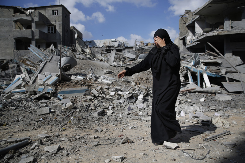 A Palestinian woman weeps as she walks amid destroyed buildings in Beit Hanoun town in the northern Gaza Strip