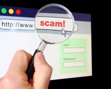 """A hand holds a magnifying glass over the location bar of a browser, revealing the URL is a """"scam""""."""