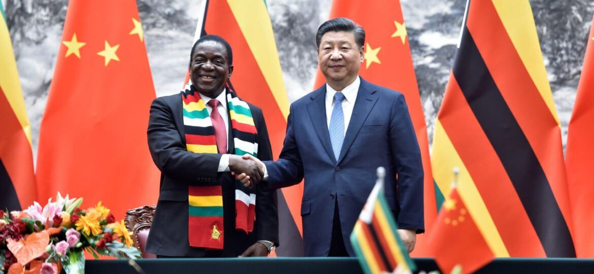Chinese President Xi Jinping shakes hands with Zimbabwean President Emmerson Mnangagwa as they pose for the media after a signing ceremony at the Great Hall of the People in Beijing
