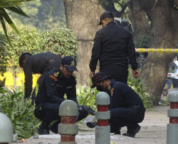 """National Security Guard soldiers inspect the site of a blast near the Israeli Embassy in New Delhi, India, Saturday, Jan. 30, 2021. A """"very low intensity"""" device exploded Friday near the Israeli Embassy in the Indian capital, but there were no injuries and little damage, police said. (AP Photo/Dinesh Joshi)"""
